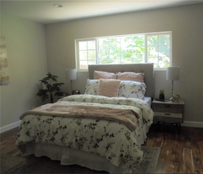 bedroom with hardwood floor, fully made bed, window, tables, lamps