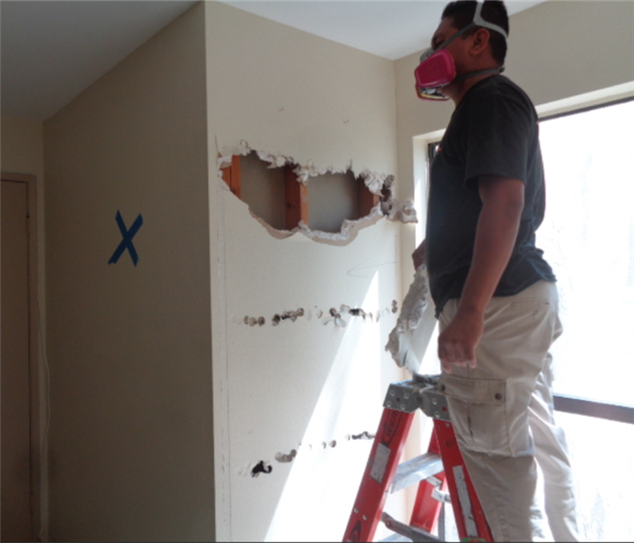 This image shows technician removing a portion of the wall.