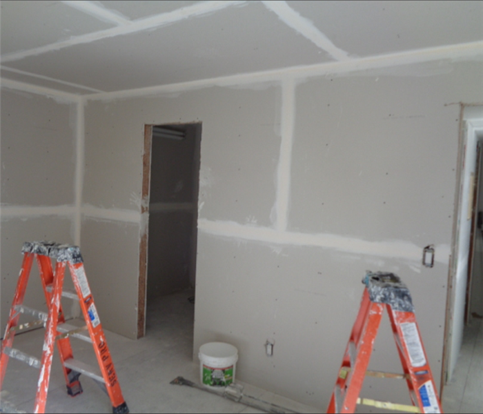 drywall is installed in room with two ladders set up