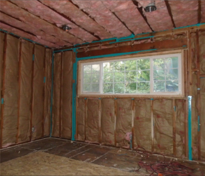 room with sheetrock removed exposing insulation and studs