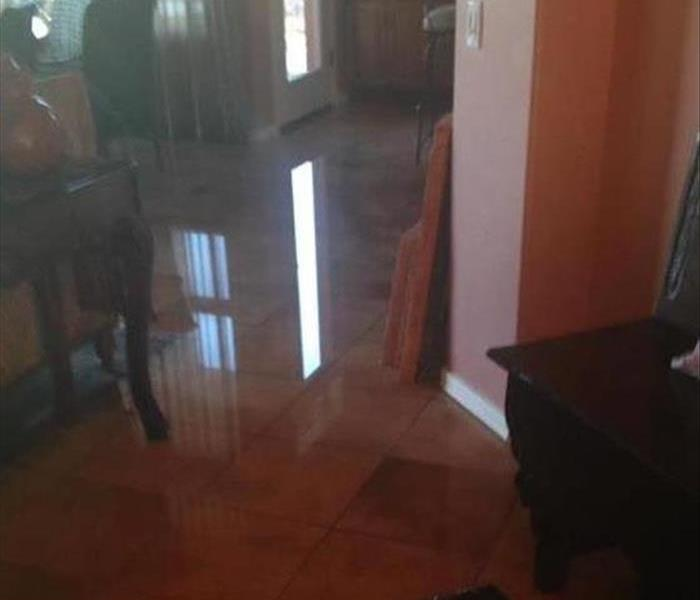 water covering tiled floor in a house, wet furniture