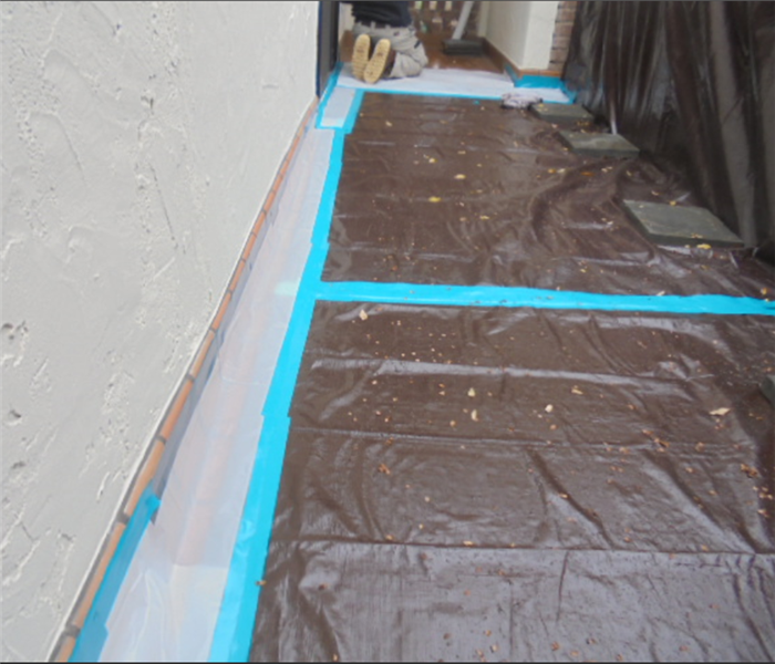 The photo shows a tarp laying over a roof