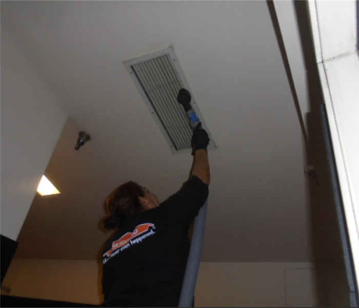 this image shows a SERVPRO employee cleaning a hvac register