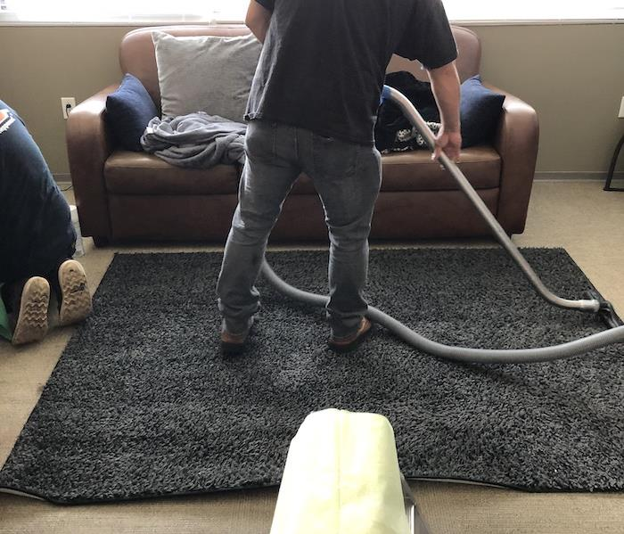 SERVPRO tech cleaning room with area rug and couch