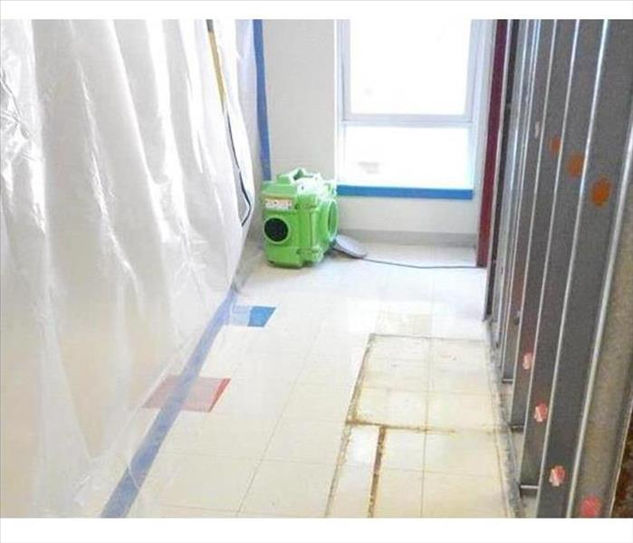 stripped wall, plastic sheeting, and a green air scrubber