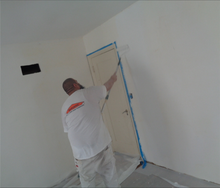 Servpro technician painting wall