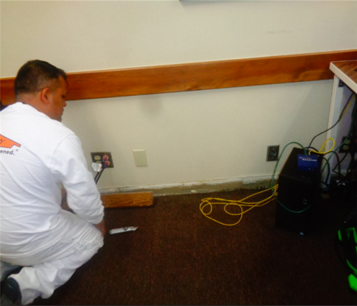 Technician removing baseboards