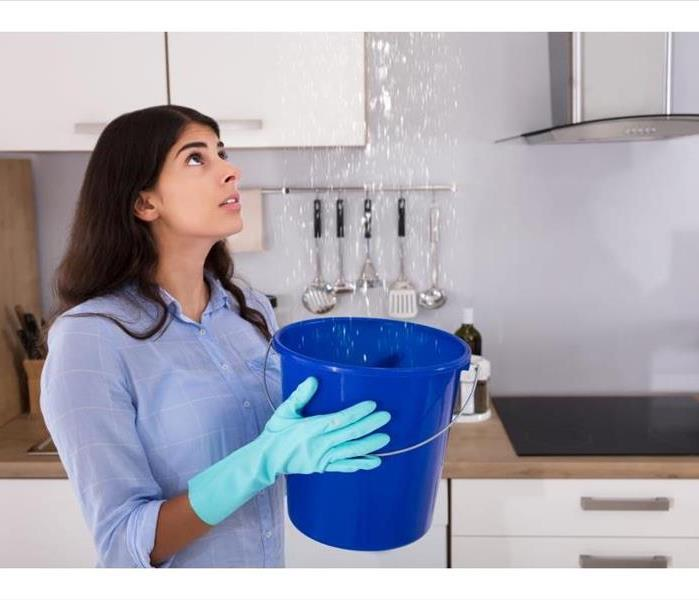 water pouring from kitchen ceiling into blue bucket that woman is holding with gloved hands
